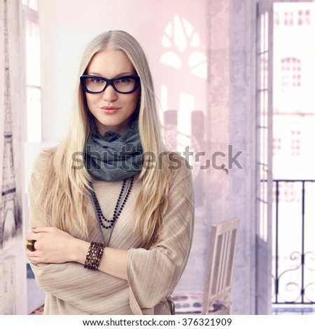 Young trendy casual caucasian blonde woman with glasses at retro home. Standing, arms crossed, smiling looking at camera. Wearing jewelry, copyspace. - stock photo