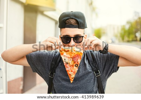 young trendy fun hipster guy doing his beard out of a piece of pizza. walking down the street, eating pizza, sunglasses, a cap, a great carefree day - stock photo
