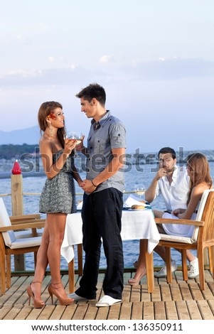 Young trendy romantic couple celebrating with glasses of wine standing on a wooden deck of an outdoor restaurant overlooking the sea
