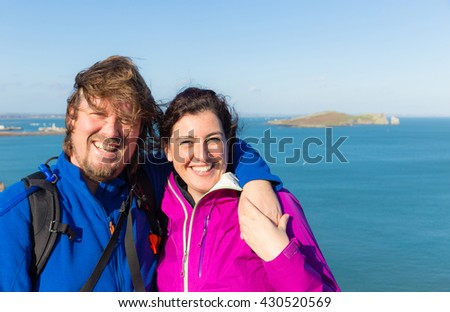 Young trendy smiling and cuddling couple in Ireland at Howth with the Irish sea in the background