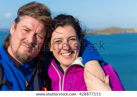 Young trendy smiling and hugging couple in Ireland wearing outdoor gear with the Irish sea in the background - stock photo