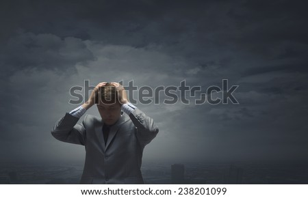 Young troubled businessman holding hands on head - stock photo