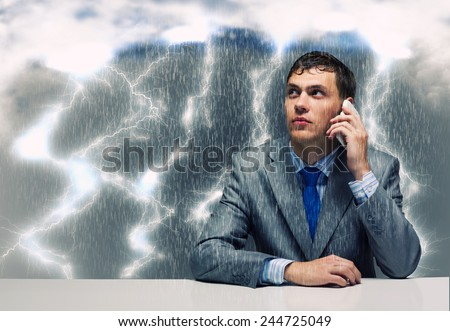 Young troubled wet businessman talking on phone - stock photo