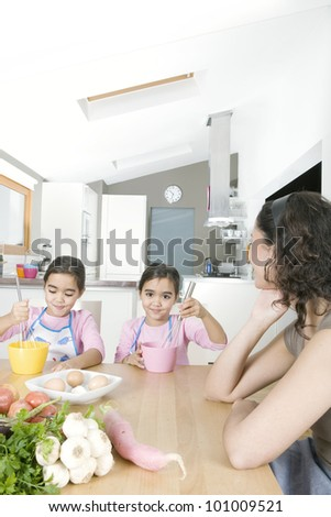 Young twin daughters beating eggs in the kitchen with mum. - stock photo