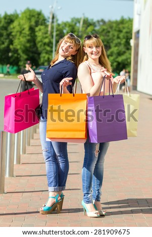 Young twin girls having fun with laughing holding shopping bags. Pretty caucasian women standing near parking waiting for a taxi - stock photo