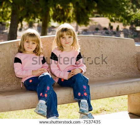 Young twin girls on park bench