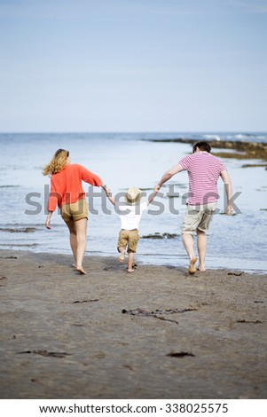 Young two parent family at the beach with their young son. They are all holding hands and swinging the little boy.  - stock photo
