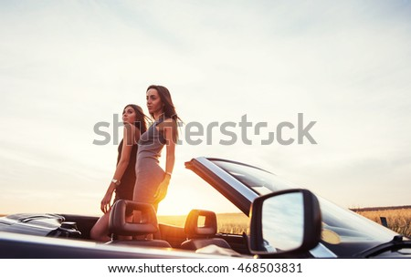 Young two women at a photo shoot. Girls gladly posing next to a black car against the sky on a fantastic sunset.