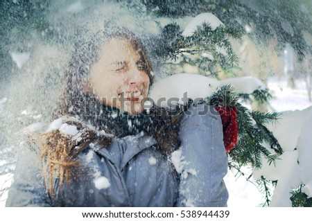 Young Ukrainian girl standing under spruce branches covered in snow in the park. The girls are wearing winter closes and squints in joy when the snow is falling on her from the tree