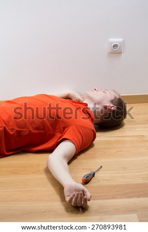 Young unconscious man lying on floor after electrocution