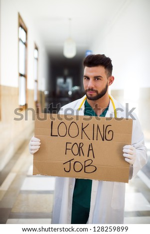 Young unemployed doctor holding a sign - stock photo