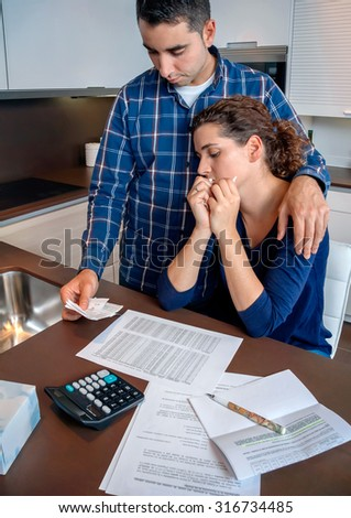 Young unemployed husband gives solace to his desperate wife crying by their debts. Financial family problems concept. - stock photo