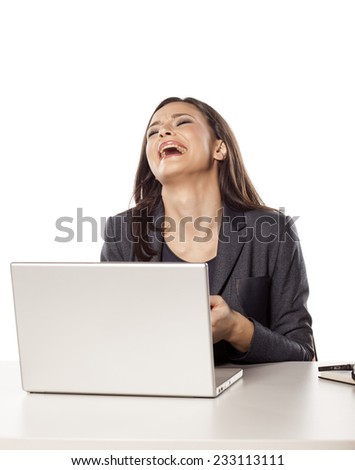 young unhappy businesswoman crying behind her laptop - stock photo