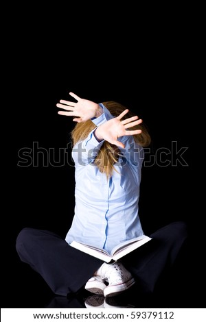 young unhappy female student with stay away gesture, keep away, studio shoot isolated on black