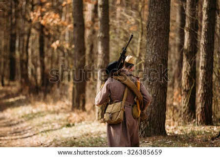 Young unidentified re-enactor dressed as Soviet soldier machine gunner goes along a forest road. - stock photo