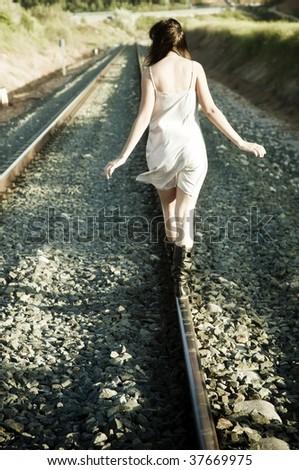 Young unrecognizable girl walking on railway - stock photo