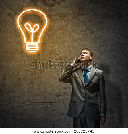Young upset businessman talking on mobile phone