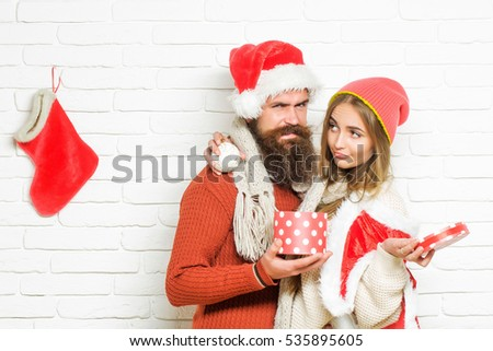 Young upset Christmas or new year couple of bearded man with gift box and pretty sexy girl or beautiful woman in red santa claus costume with xmas bauble and sock on white brick wall