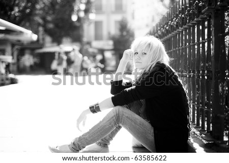 Young urban blond girl staring at camera on urban background - stock photo