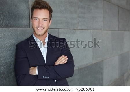 Young urban business man leaning on wall