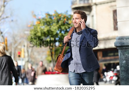 Young urban businessman on smart phone running in street talking on smartphone smiling wearing jacket and leather laptop bag on Passeig de Gracia, Barcelona, Catalonia, Spain. - stock photo