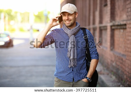 Young urban businessman professional on smartphone walking in street using app texting sms message on smartphone