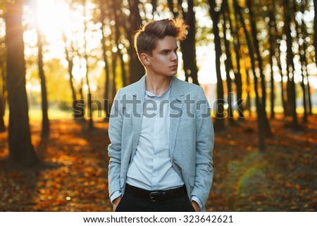 Young urban businessman professional walking in park at sunset. - stock photo
