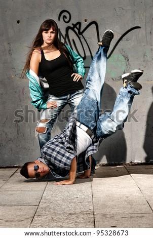 Young urban couple dancers hip hop dancing urban scene - stock photo