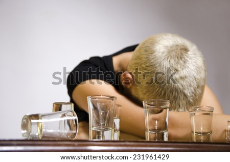 Young urban girl with blonde short hair sick from alcohol laying on table covering her face with hands. Gray gradient background.  - stock photo