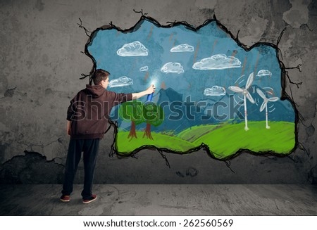 Young urban painter drawing colorful future image on the wall - stock photo