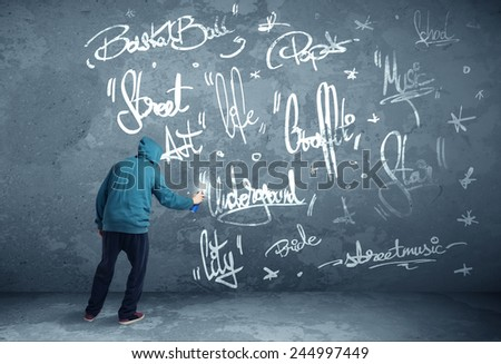Young urban painter drawing graffiti on the wall  - stock photo