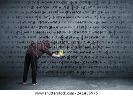 Young urban painter drawing random letters on the wall  - stock photo