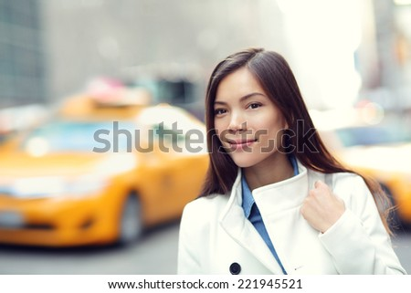 Young urban professional business woman in New York City Manhattan. Woman walking in street wearing coat downtown with yellow taxi cabs in background. Multiracial Asian Caucasian businesswoman in USA. - stock photo