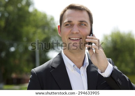 Young urban professional man talking on smartphone. Close up portrait of male business man on smart phone outdoors in suit jacket. Handsome modern guy. - stock photo