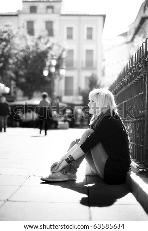 Young urban thougthful blonde  on urban background - stock photo