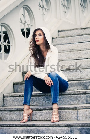young urban woman in blue jeans and high heel sandals sit on stairs full body shot