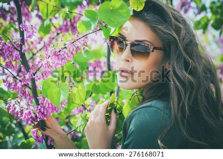 young urban woman with sunglasses outdoor shot among the spring flowers tree - stock photo
