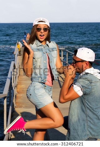 Young valentine couple in love outdoor. closeup fashion portrait of young beautiful stylish couple in summer on the sea pier. Fun and smile. Romantic Sunset together,going crazy.Marry me please - stock photo
