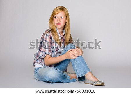 young very attractive female sits on floor, studio shoot on grey background