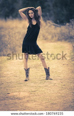 Young very thin girl posing outdoors in a black dress and boots - stock photo