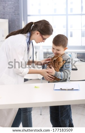 Young vet helping little boy holding rabbit at pets' clinic.