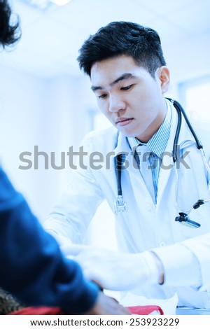 Young veterinarian working at hospital take with blue filter - stock photo