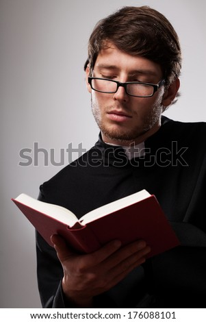 Young vicar wearing black cassock studying Holy Scripture from Bible - stock photo