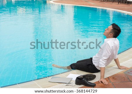 Young Vietnamese businessman relaxing at poolside with legs in water