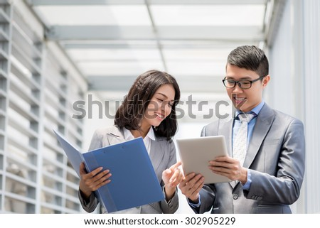 Young Vietnamese businessman showing application to her beautiful colleague