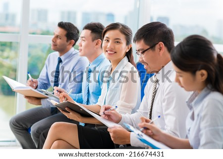 Young Vietnamese businesswoman smiling at the camera during a presentation - stock photo