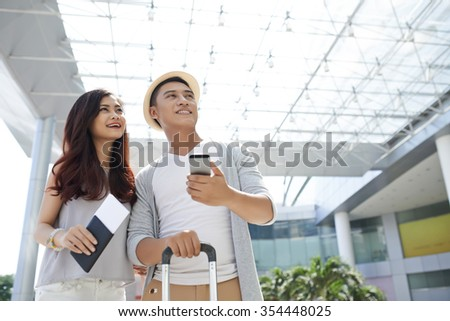 Young Vietnamese couple in the airport waiting for departure - stock photo