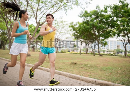 Young Vietnamese couple jogging in the park - stock photo