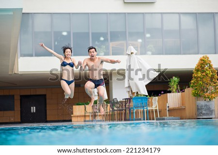 Young Vietnamese couple jumping into the swimming pool - stock photo