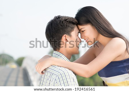 Young Vietnamese couple looking at each other - stock photo